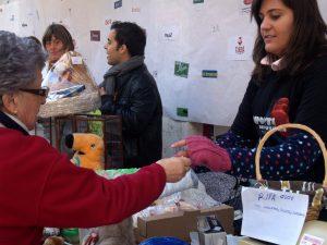 Una señora compra un número de la rifa solidaria.