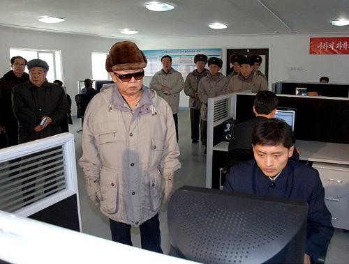 Gente que mira a Kim Jong-Il mientras él mira un ordenador.