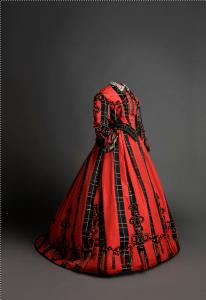 Traje. 1865 - 1868. En satén de color negro y coral con decoración de aplicación de pasamanería (Museo del Traje. CIPE)