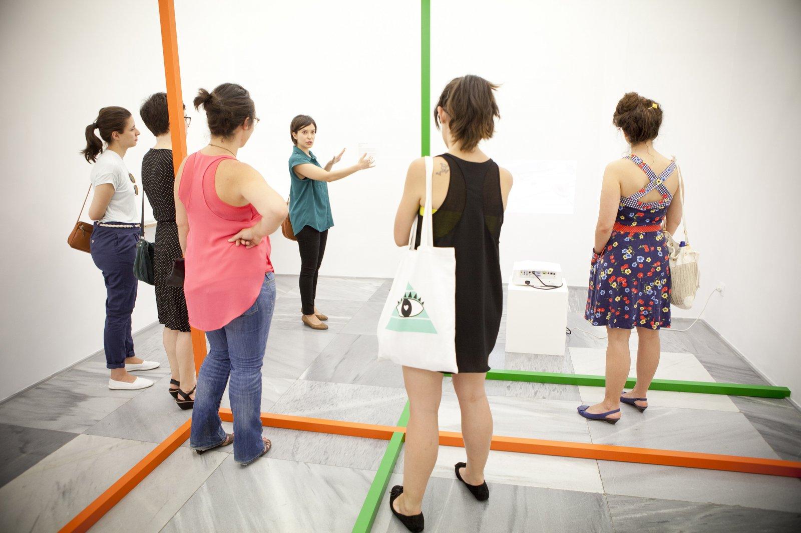 Elena Zapata, de Hablar en Arte, y un grupo de visitantes en Espacio Mínimo