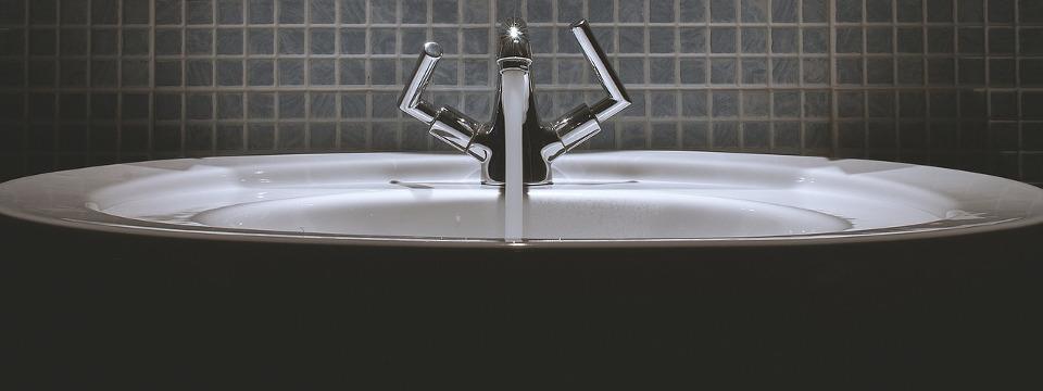 Lavabo de baño con agua abierta.