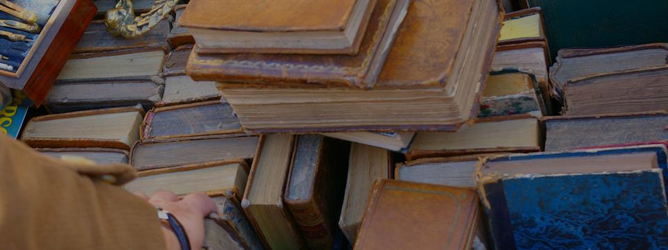 Mano rebuscando en montaña de libros