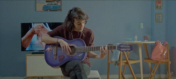 Fotograma del filme con Joy tocando la guitarra.